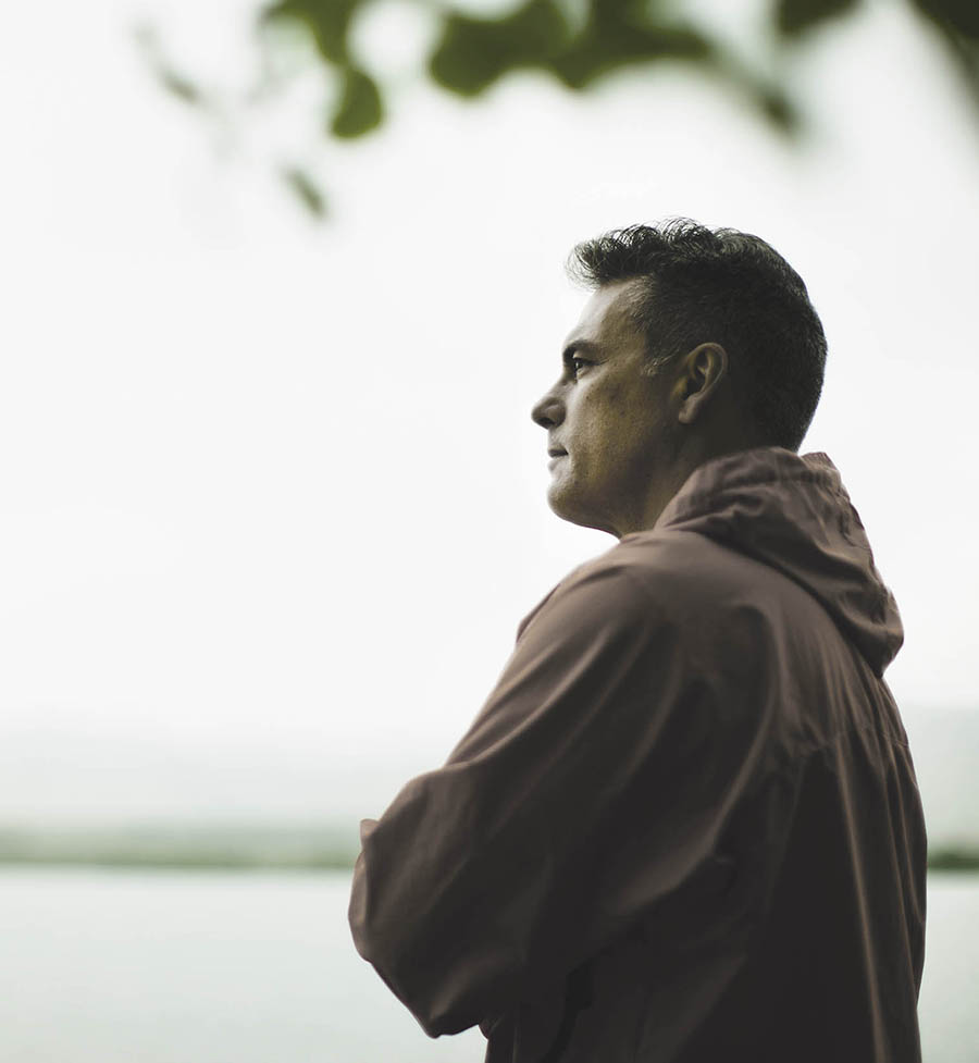 Man in Landscape,USA,A middle aged man in a red jacket looking over water, deep in thought.